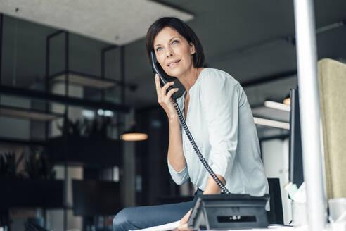 Mature businesswoman talking through landline phone in office - JOSEF03821
