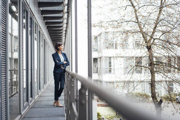 Mature businesswoman with arms crossed on office balcony - JOSEF03830