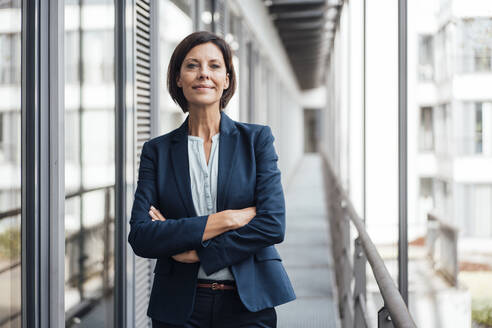 Smiling confident businesswoman with arms crossed standing on balcony - JOSEF03833
