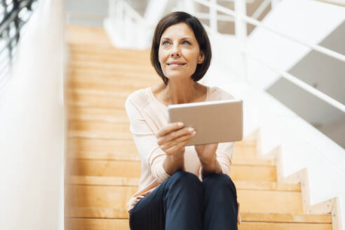 Mature businesswoman with digital tablet sitting on steps in corridor - JOSEF03839
