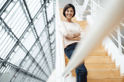 Mature female entrepreneur with arms crossed standing on steps - JOSEF03842