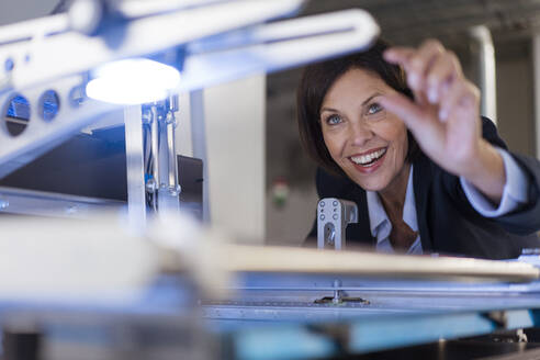 Smiling businesswoman analyzing machinery at illuminated industry - JOSEF03854