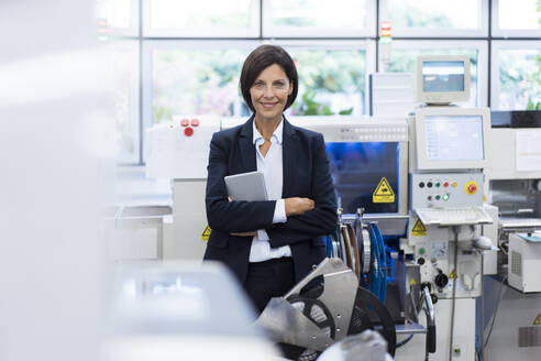 Confident businesswoman with arms in factory - JOSEF03860