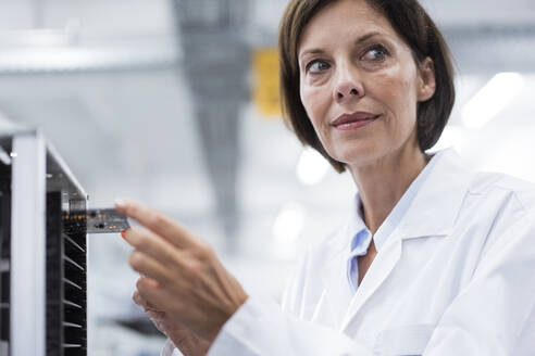 Mature female technician by machinery in industry - JOSEF03875