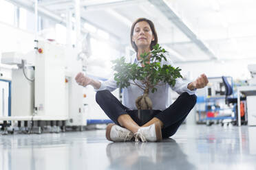 Female entrepreneur meditating while sitting on floor in industry - JOSEF03890
