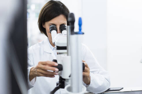 Female scientist using microscope at laboratory - JOSEF03893