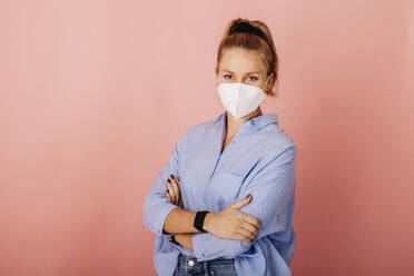 Businesswoman wearing FFP2 face mask standing with arms crossed against colored background - DAWF01783