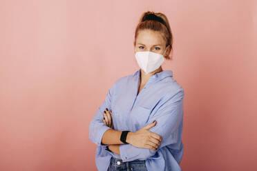 Frau mit FFP2 Maske vor Rosa Beige Hintergrund. Österreich, Kärnten, Klagenfurt - DAWF01783