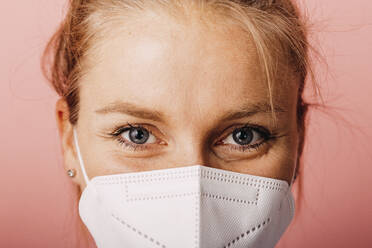 Close-up of woman wearing protective face mask against colored background - DAWF01786
