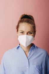 Frau mit FFP2 Maske vor Rosa Beige Hintergrund. Österreich, Kärnten, Klagenfurt - DAWF01789
