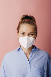 Mid adult businesswoman wearing protective face mask staring while standing against colored background - DAWF01789