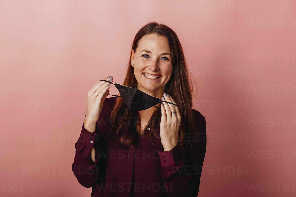 Frau mit FFP2 Maske vor Rosa Beige Hintergrund. Österreich, Kärnten, Klagenfurt - DAWF01792 - Daniel Waschnig Photography/Westend61