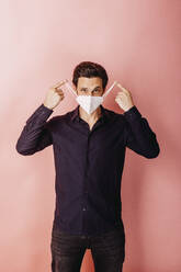 Male entrepreneur wearing protective face mask standing against colored background - DAWF01798