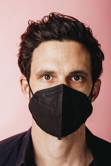 Businessman wearing black color protective face mask staring while standing against colored background - DAWF01801