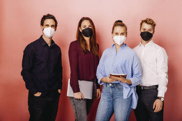 Confident business people wearing protective face mask standing against colored background - DAWF01804
