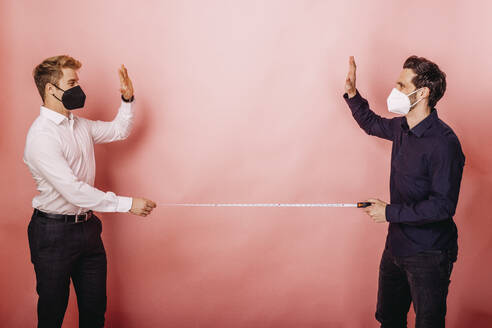 Business people holding measuring tape while giving high-five standing distant against colored background - DAWF01807