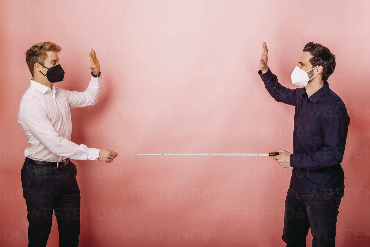 Business people holding measuring tape while giving high-five standing distant against colored background - DAWF01807 - Daniel Waschnig Photography/Westend61