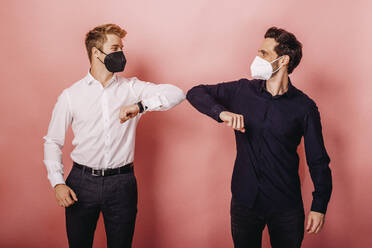 Male entrepreneurs wearing protective face mask greeting with elbow bumps while standing against colored background - DAWF01810