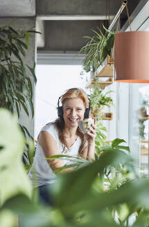 Happy woman holding coffee cup while listening music through headphones while sitting in loft apartment - FMKF06975