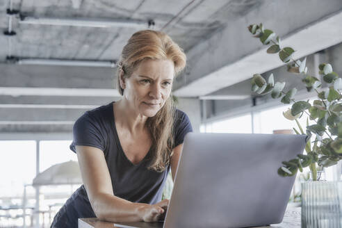 Mature woman using laptop while leaning at table in loft apartment at home - FMKF06984