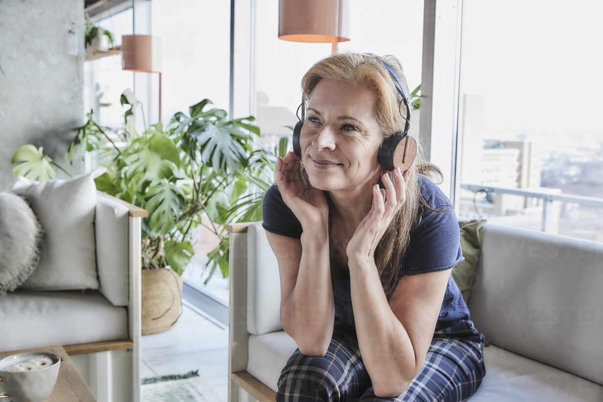 Lächelnde reife Frau schaut weg, während sie Musik über Kopfhörer auf dem Sofa zu Hause hört - FMKF06990 - Jo Kirchherr/Westend61