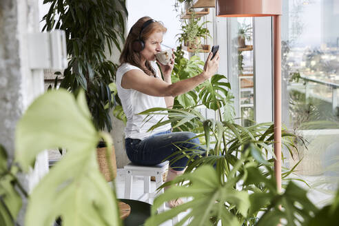 Woman with headphones taking selfie while drinking coffee on stool in loft apartment at home - FMKF06999
