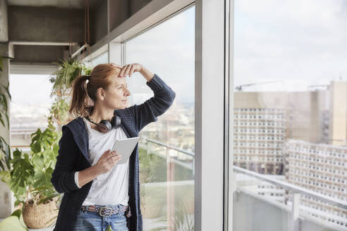Woman with headphones holding digital tablet while looking through window - FMKF07002