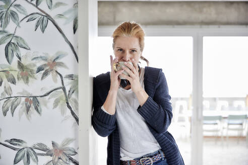 Woman drinking coffee while leaning on wall against window at home - FMKF07005