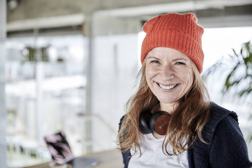 Smiling businesswoman with knit hat at home office - FMKF07011