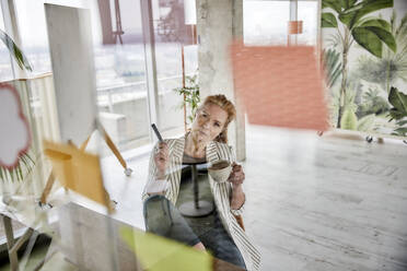 Female entrepreneur holding coffee cup while doing business plan seen through glass wall at office - FMKF07020