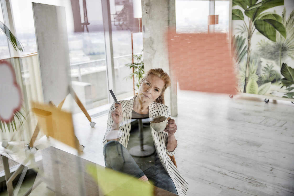 Female entrepreneur holding coffee cup while doing business plan seen through glass wall at home office - FMKF07020 - Jo Kirchherr/Westend61