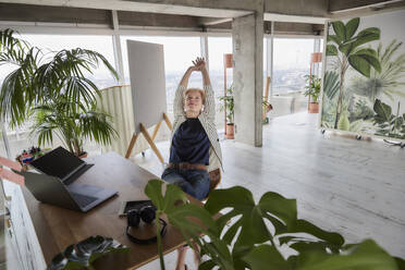 Female entrepreneur relaxing while sitting at desk in home office - FMKF07026