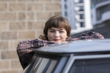 Young woman smiling while leaning on car roof - SGF02764