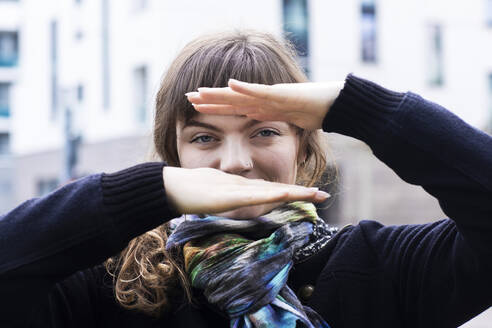 Smiling woman looking through hand gesture while standing outdoors - SGF02773