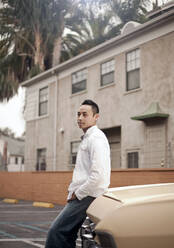 Portrait of young man (23-30) standing by car, Los Angeles, USA - AJOF01080