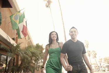Smiling couple holding hands while walking outdoors - AJOF01089
