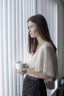Young woman with coffee cup looking away while standing by window at home - AJOF01091