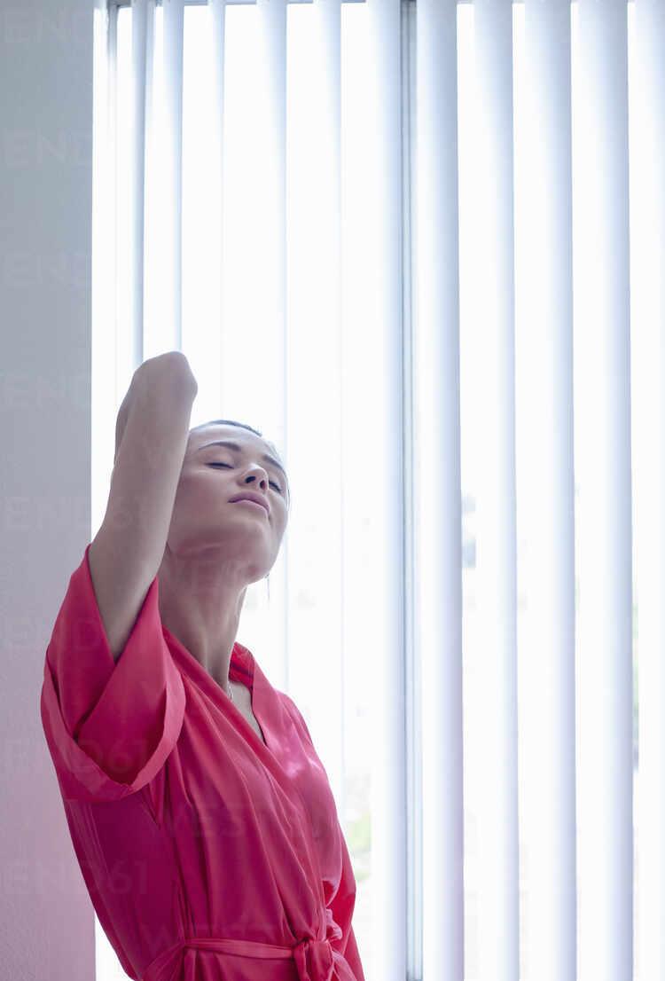 Frau streckt die Hände, während sie zu Hause am Fenster steht - AJOF01097 - LOUIS CHRISTIAN/Westend61