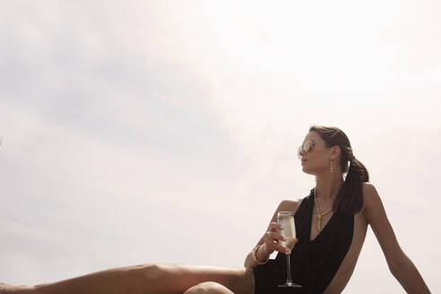 Woman in one piece swimsuit having champagne while relaxing against sky - AJOF01103