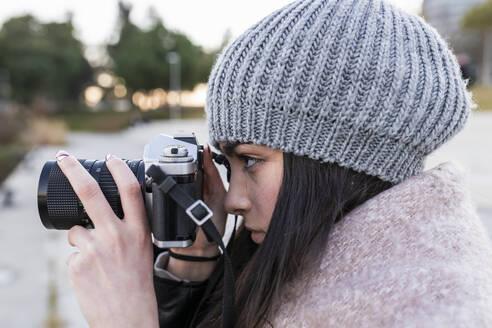 Teenage girl photographing through camera outdoors - JRVF00285