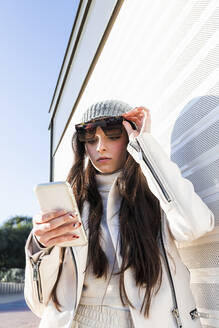 Teenager girl with long hair in sunglasses using mobile phone against white wall - JRVF00300