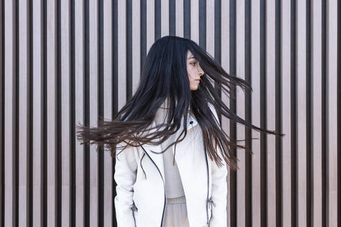 Teenage girl with tousled hair against wall - JRVF00306