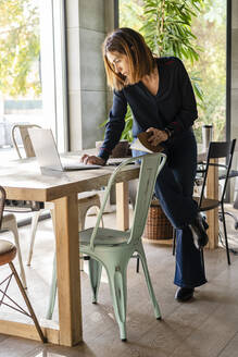 Female entrepreneur using laptop while sitting on conference table in office - DLTSF01629