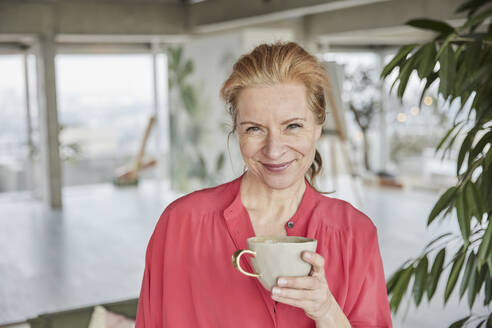 Smiling mature woman holding coffee cup at home - FMKF07043