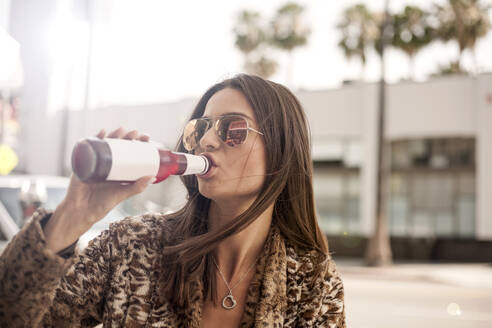 Beautiful woman in sunglasses drinking from bottle at city - AJOF01107