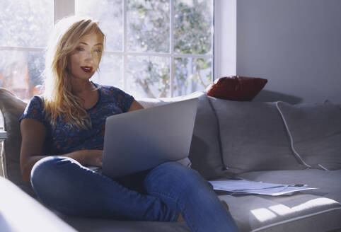 USA, Florida, Beautiful woman sitting on the couch and working on the laptop computer at home - AZF00194