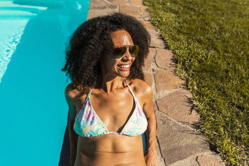 Smiling Afro woman sitting at swimming pool during sunny day - AKLF00076