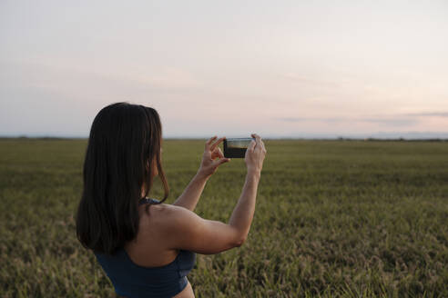 Woman taking selfie through mobile phone while standing at meadow - AMPF00082