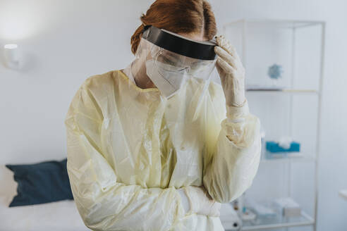 Female healthcare worker wearing protective workwear standing with hand in hand at examination room - MFF07405