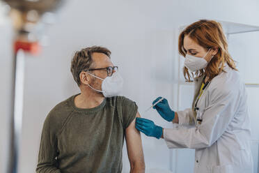 General practitioner injecting COVID-19 vaccine in patient arm while standing at examination room - MFF07432
